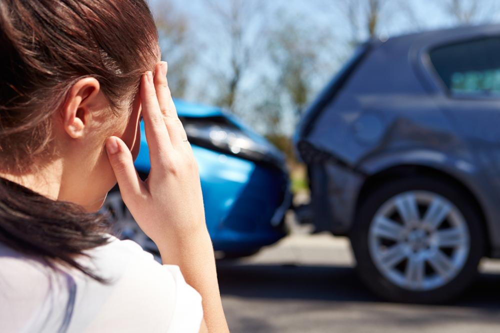 woman holding her head in pain with an auto accident in the background