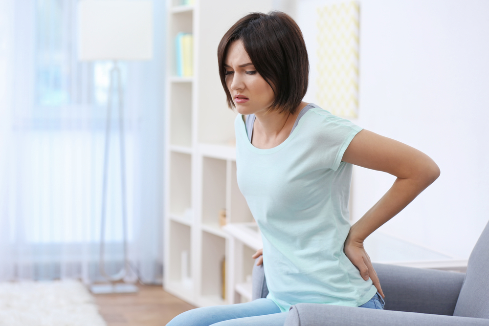 woman holding her back from chronic pain
