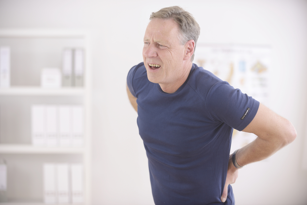 man holding his lower back in discomfort